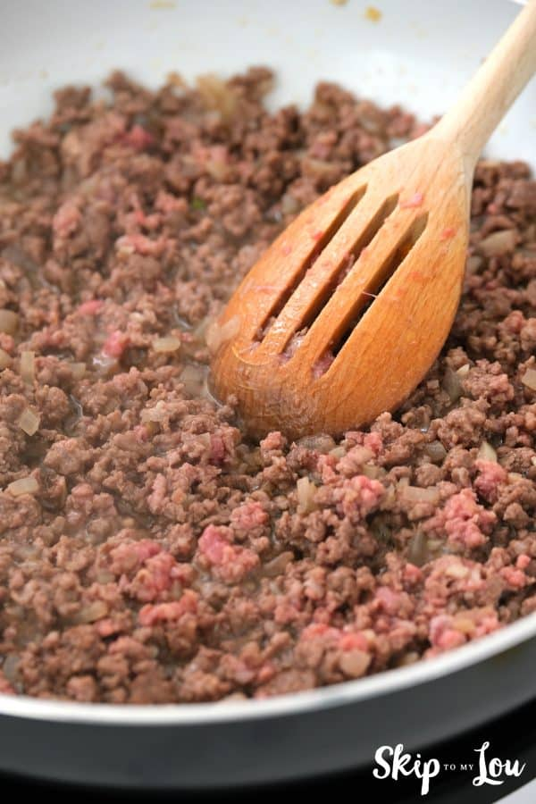 ground beef browning in a skillet with a slotted spoon stirring it