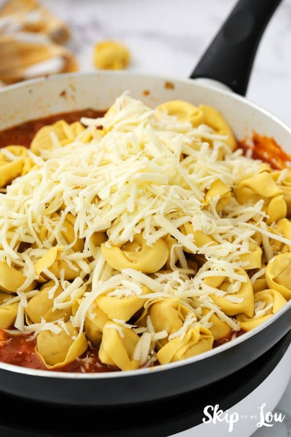 cooked tortellini and mozzarella cheese have been added to the sauce mixture in the skillet