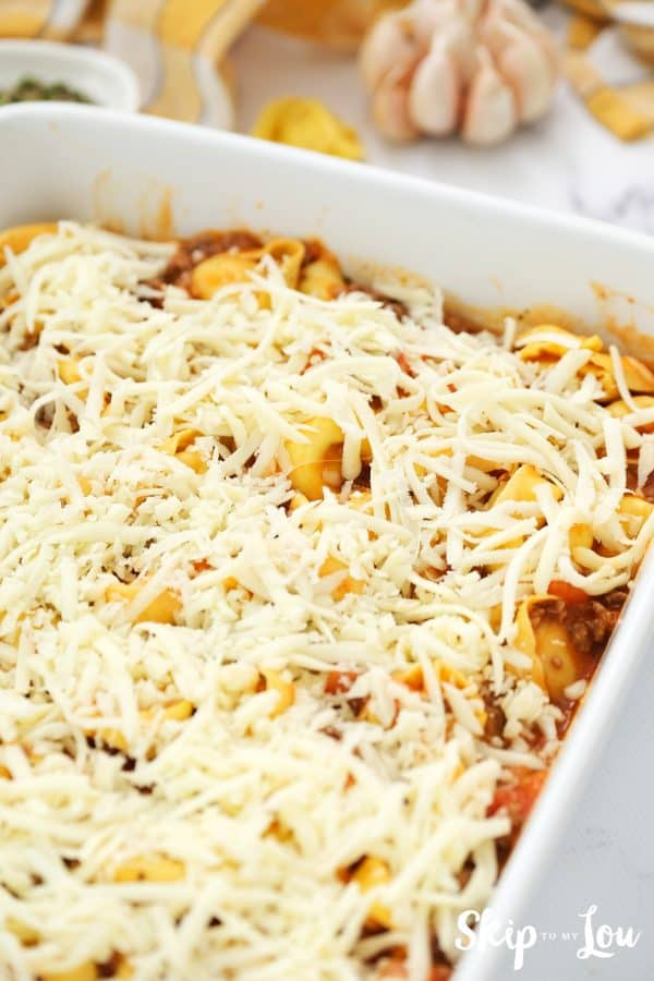 tortellini and meat sauce have been transferred to white casserole dish and covered with grated cheese