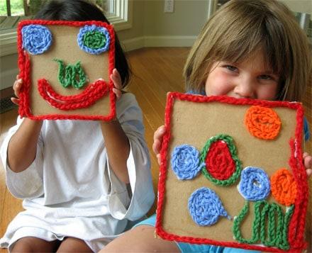 preschool children holding yarn mosaics