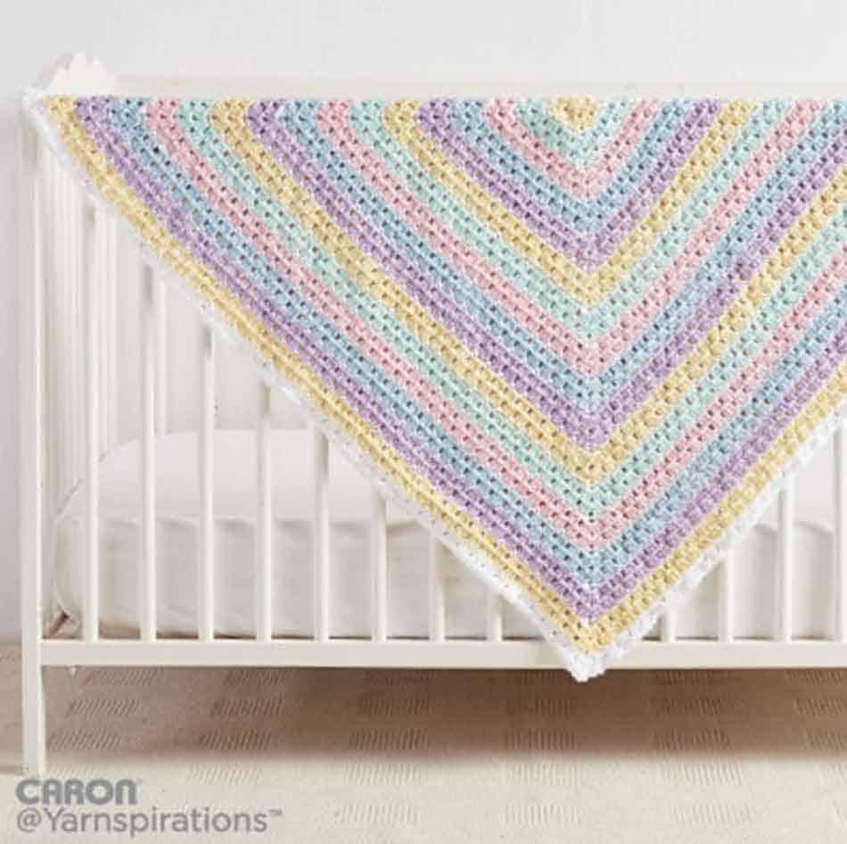 pastel rainbow blanket on white crib