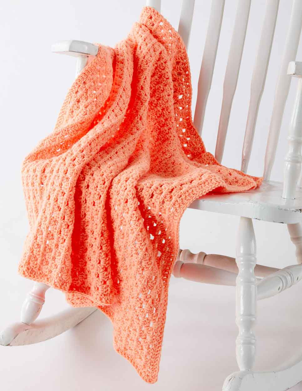 peach crochet blanket on white rocking chair