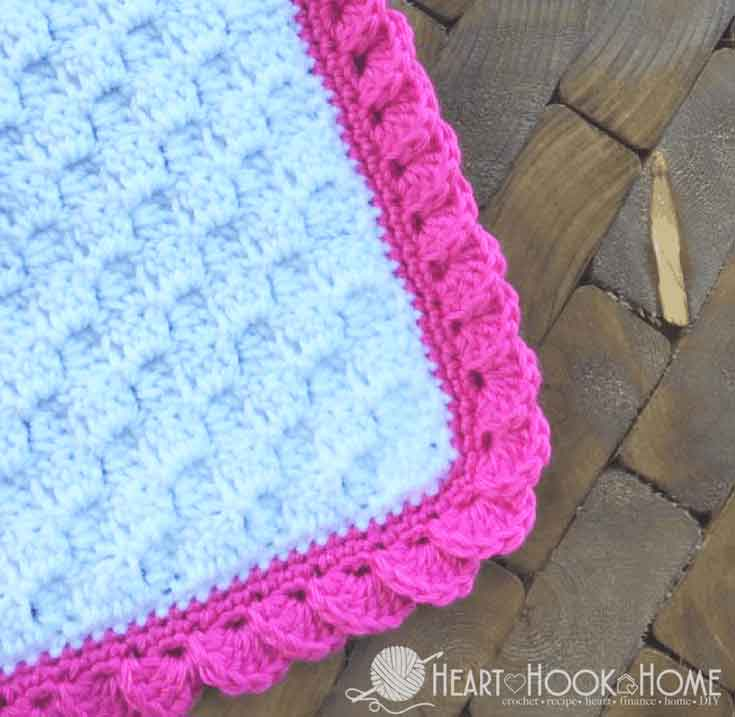 white blanket with pink reverse shell border