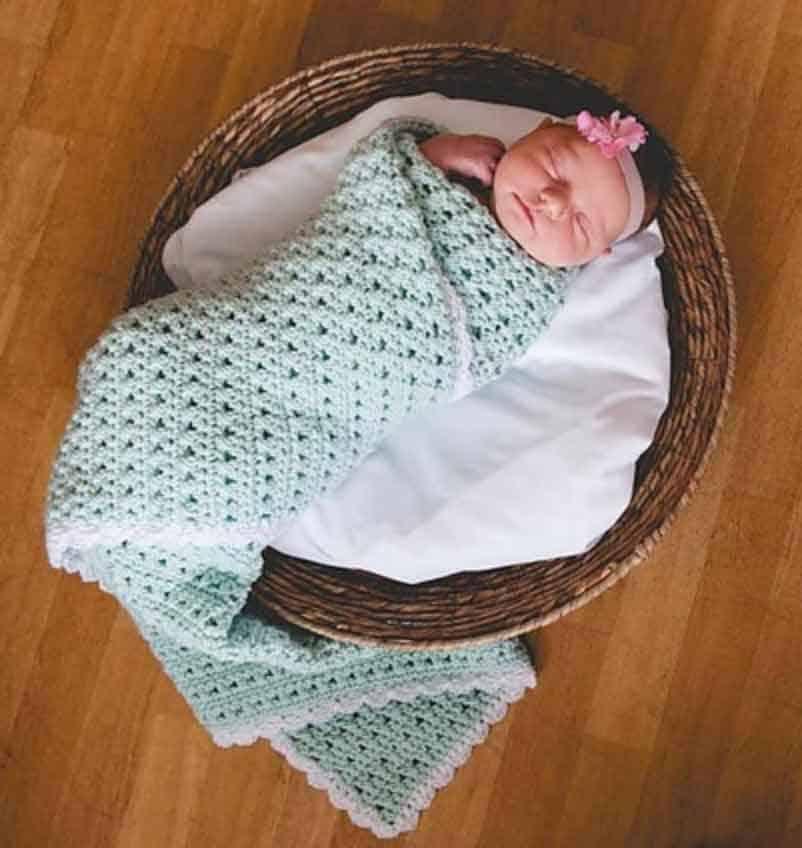 baby swaddled in mint green crochet blanket sleeping in basket