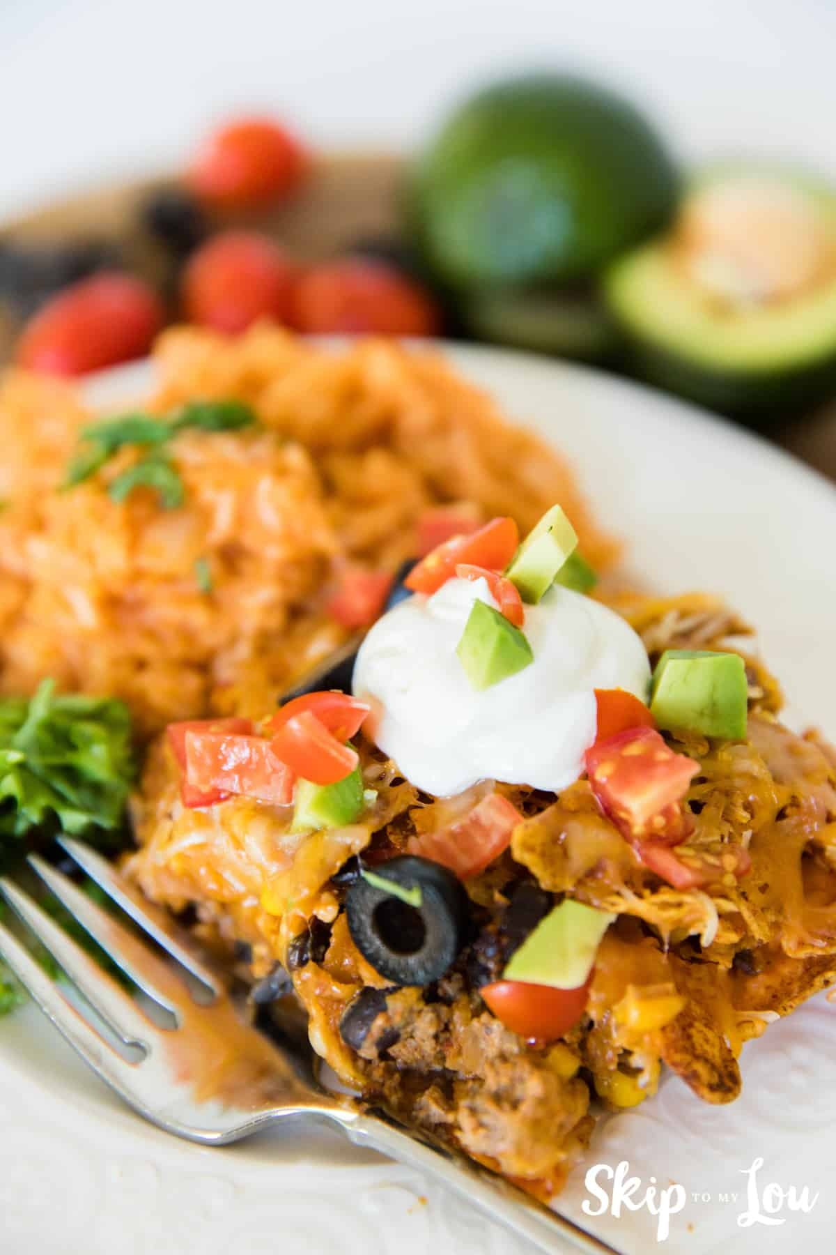 Doritos casserole topped with sour cream and served with mexican rice on the side