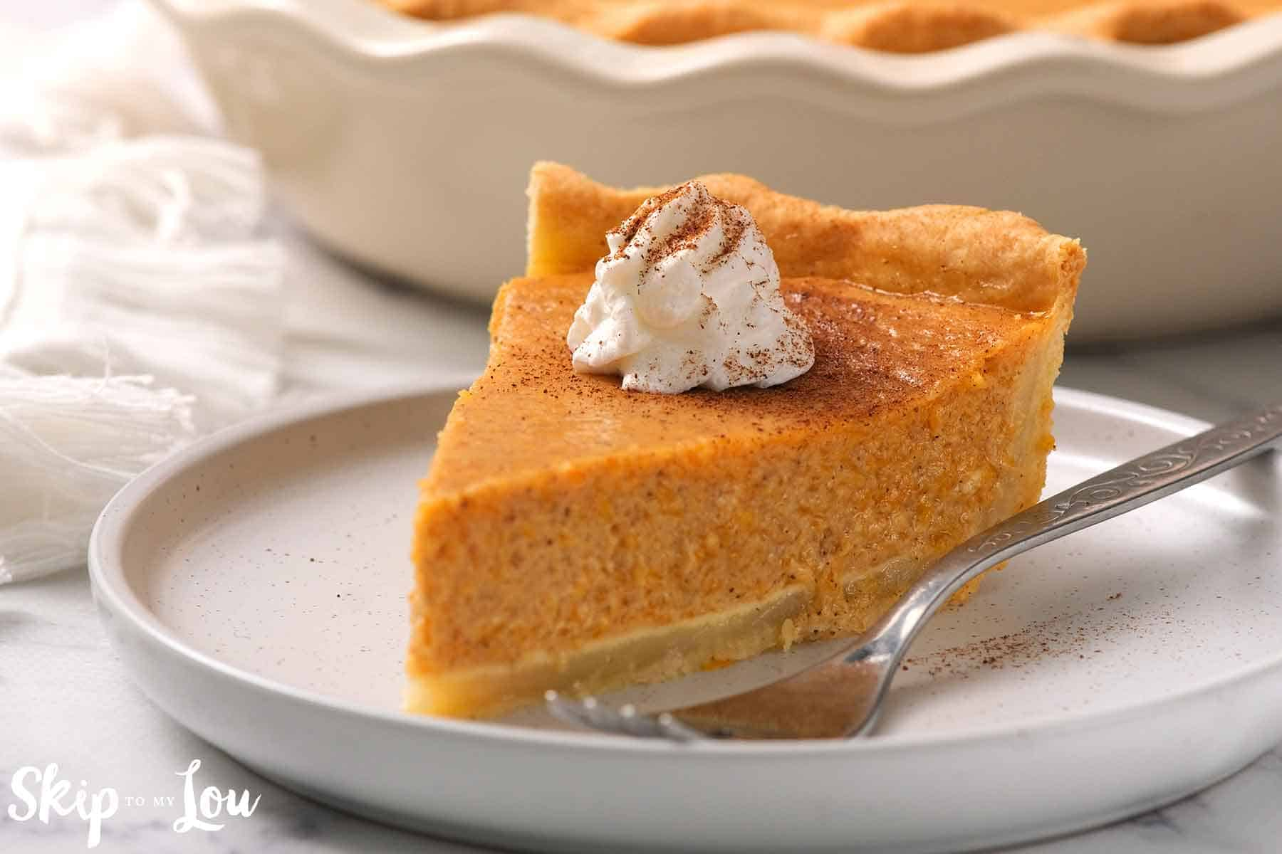 slice of pumpkin pie on white plate with fork