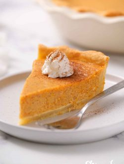 slice of pumpkin garnished with whipped cream and dusting of cinnamon
